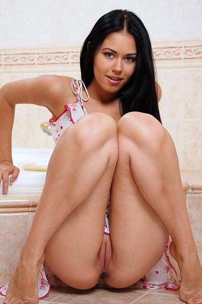 Молодая голая брюнетка с лысой писькой позирует в ванной