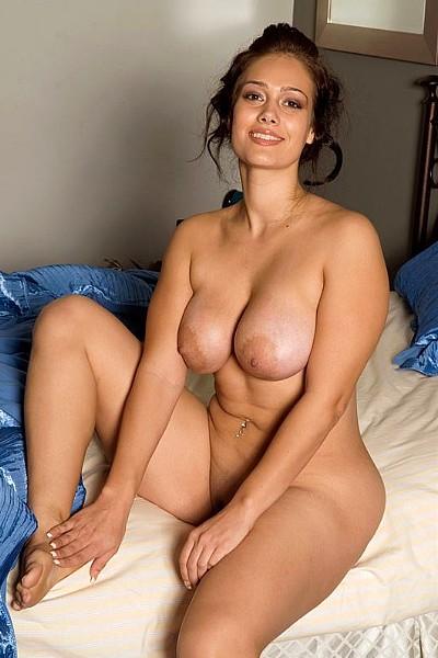 Красивая женщина с большой грудью позирует голая в спальне