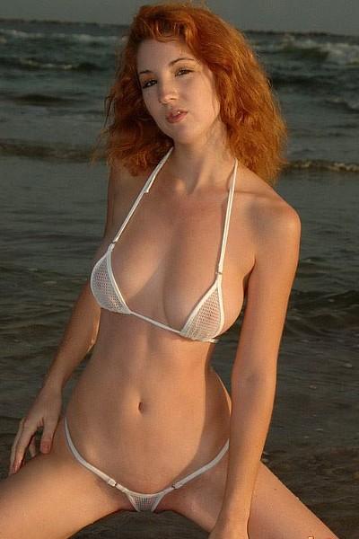 Красивая рыжая девка с большими сиськами в мини бикини позирует на берегу моря