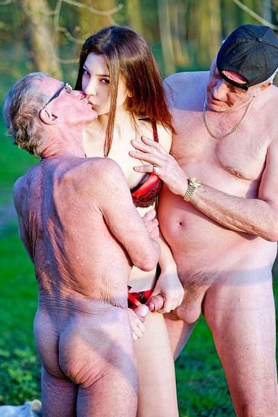 В лесу молоденькая потаскушка трахается с двумя пожилыми мужчинами и сосет у них старые члены