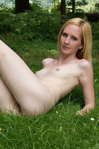 Девица с маленькими сиськами позирует голая в лесу