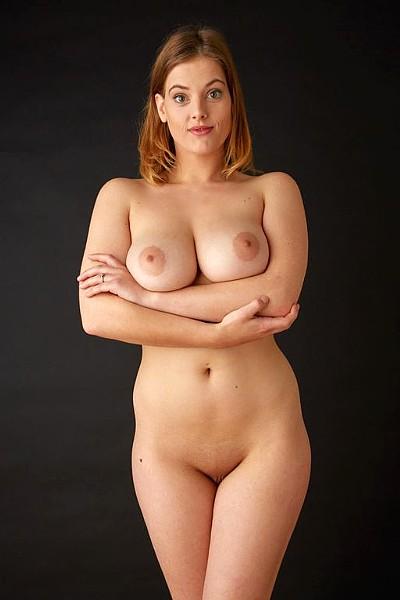 Рыжая девушка с большими натуральными сиськами и лысой пиздой сняла сорочку и позирует голая